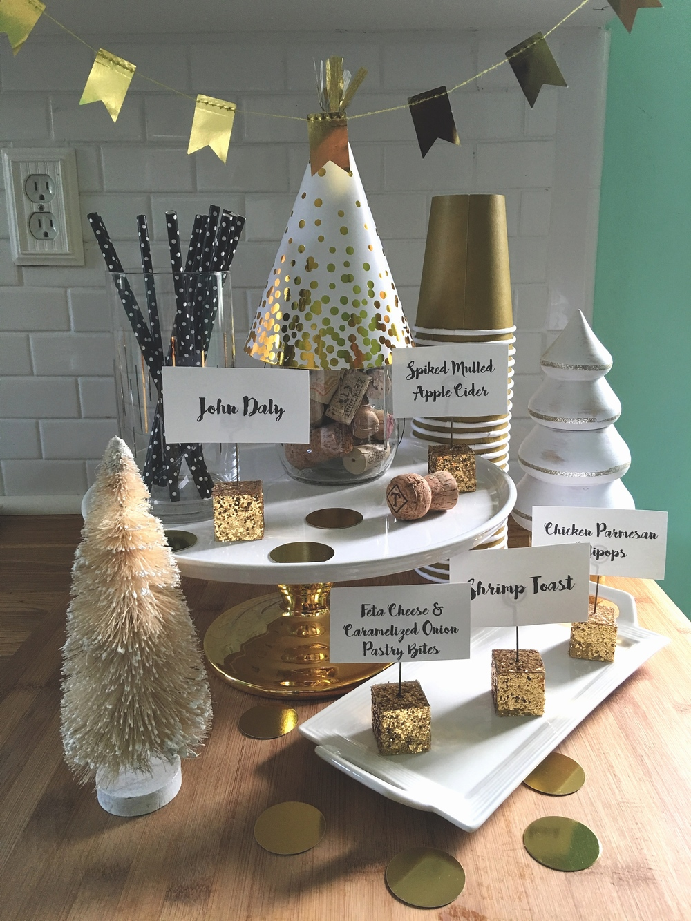 I had decided that the color palette was gold, black, and white, so these are the colors I looked for in each of the decor items chosen. I was lucky to have a 20% off coupon for Target, so this is where I picked up garland, confetti, party hats, and the paper straws. I found an amazing cake stand with a gold base and several rectangular, white platters at Homegoods. At Party City, I purchased the gold paper cups and the gold glittered place card holders to display the names of the batch cocktails and what each appetizer was.