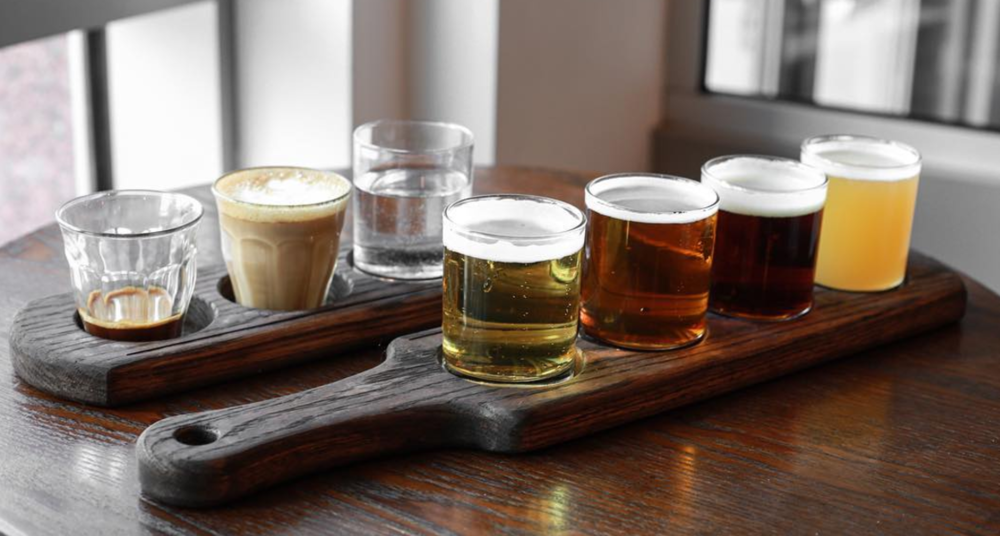 Beer Flight - 4 of 10oz beer sampler on tap.Behind is the picture of