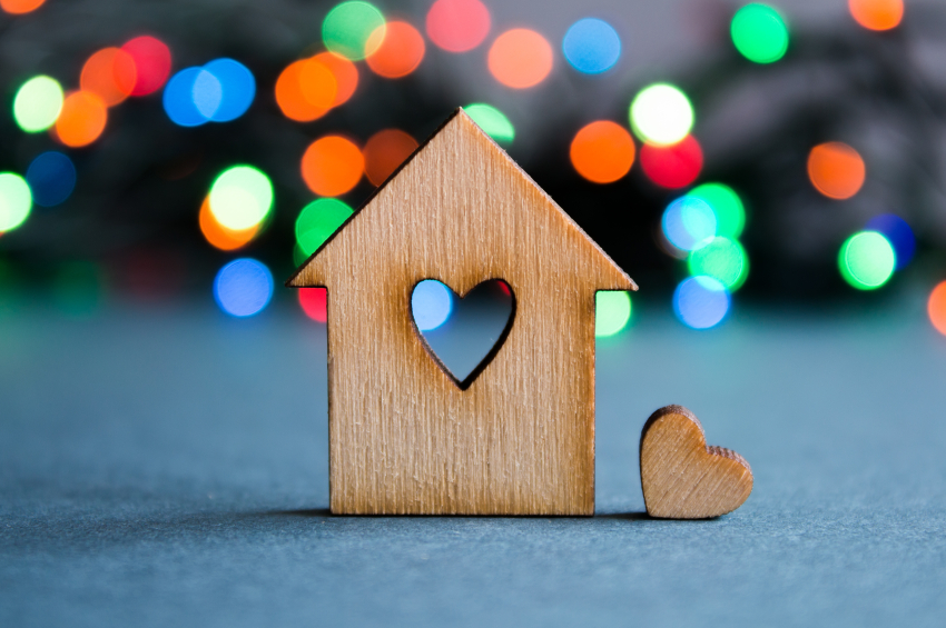Wooden house with hole in the form of heart with little heart on
