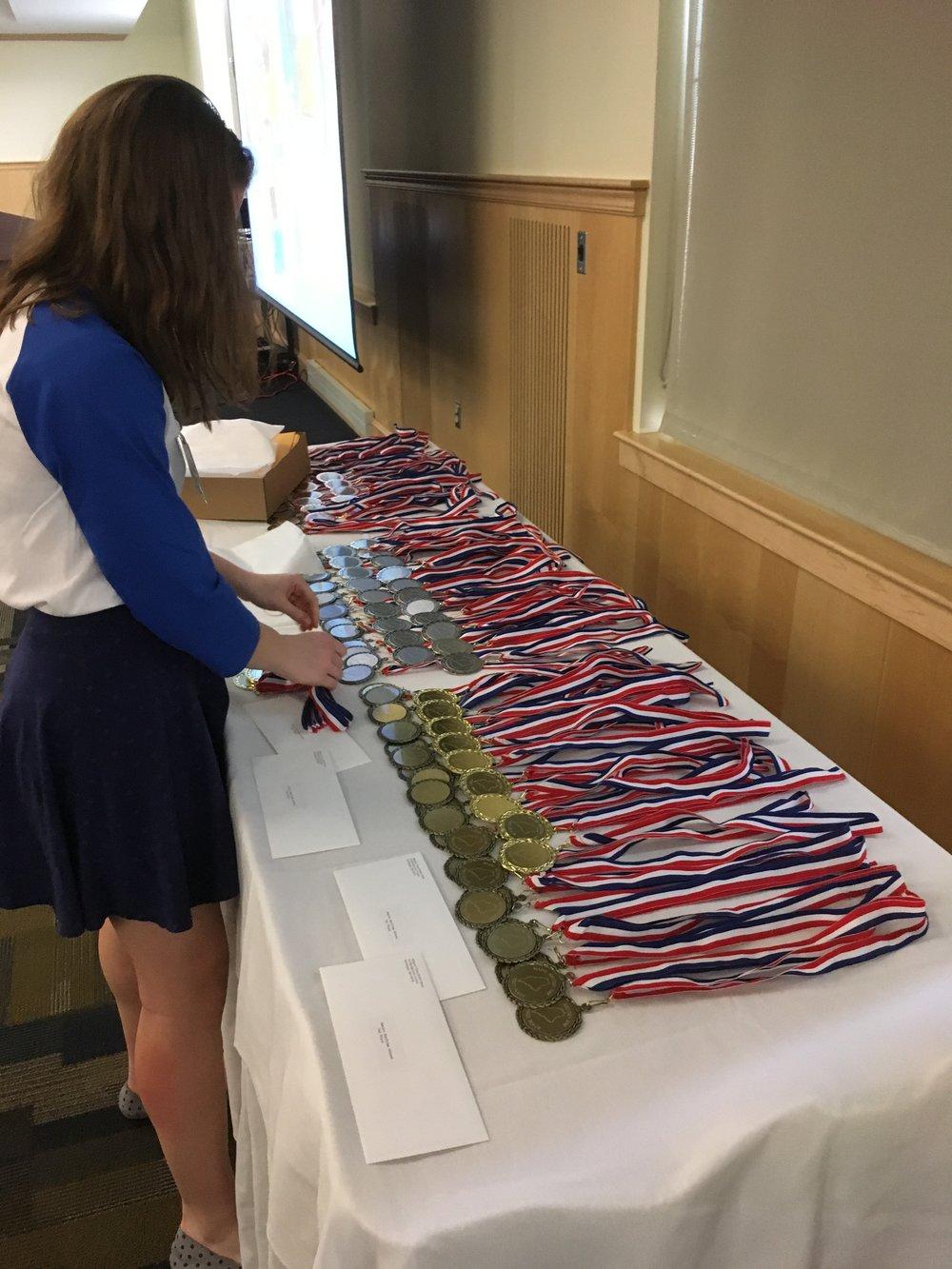Assistant Coordinator Avery Arena Arranging Medals.jpg