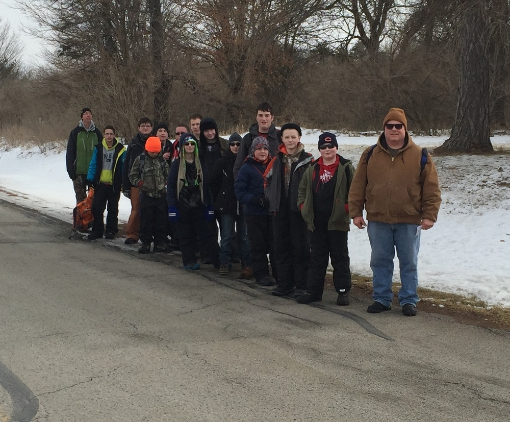Boy Scouts accessing their campsite by walking alongside the road