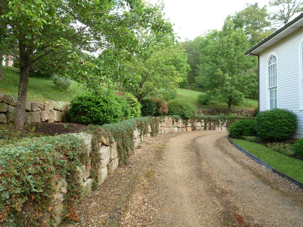 The natural stone retaining walls are terraced and landscaped