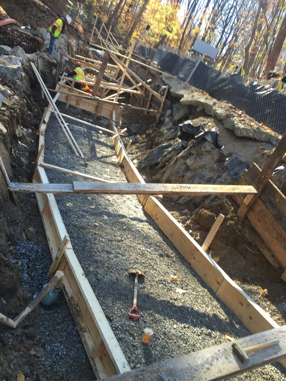 The subgrade is dewatered and stabilized using stone; formwork nearly complete and location verified by a survey crew