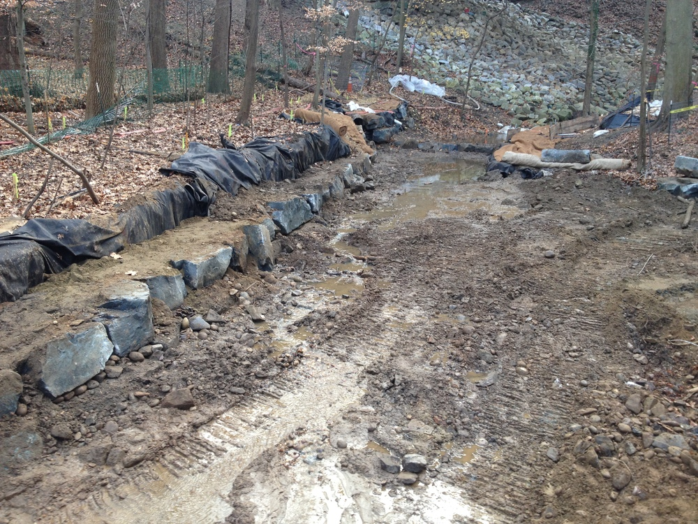 Geotextile is placed along the stream banks prior to stone placement to prevent soil from washing out from behind
