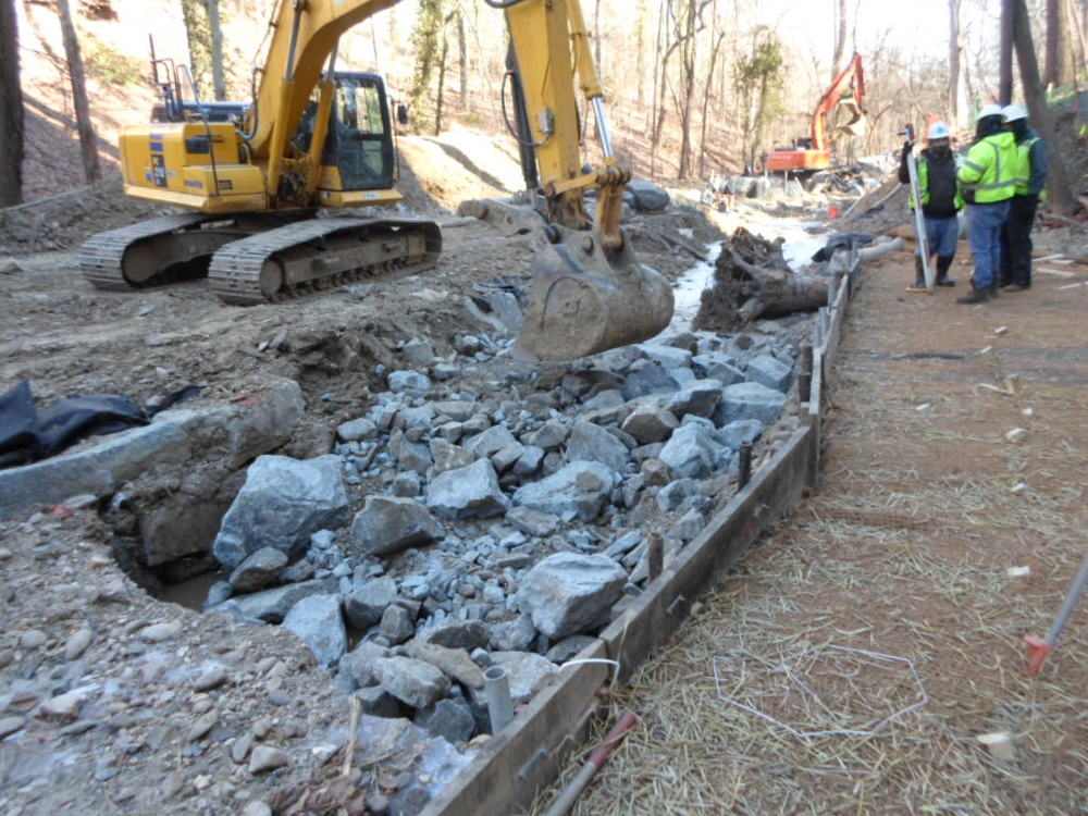 The contractor sets a specified mix of stones and river rocks in the riffle grade control.