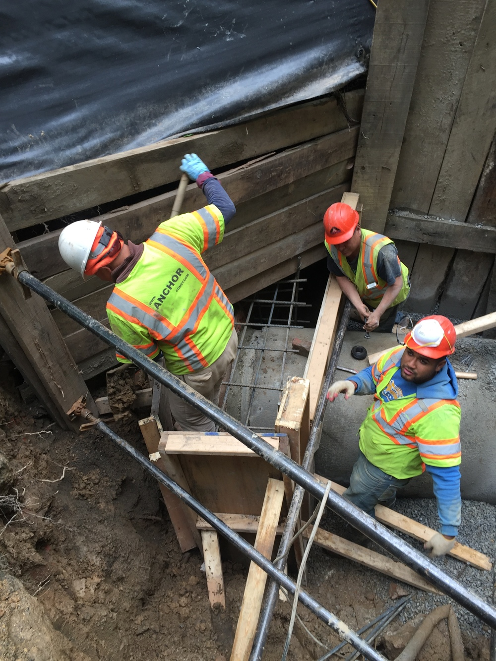 The crew constructs the concrete collar to be placed around the seam between the new and old culvert. Formwork and rebar are installed.