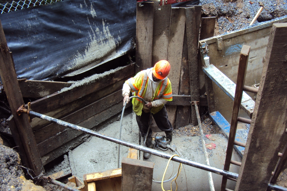 Fresh concrete placed for the collar. A crew member vibrates the fresh concrete to ensure that the aggregate in the concrete mix distributes evenly across the collar.