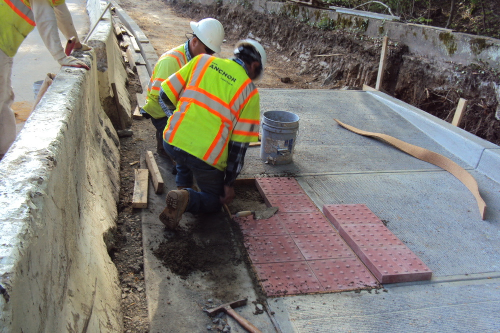 Placing detectable warning surface pavers at the ramp landing