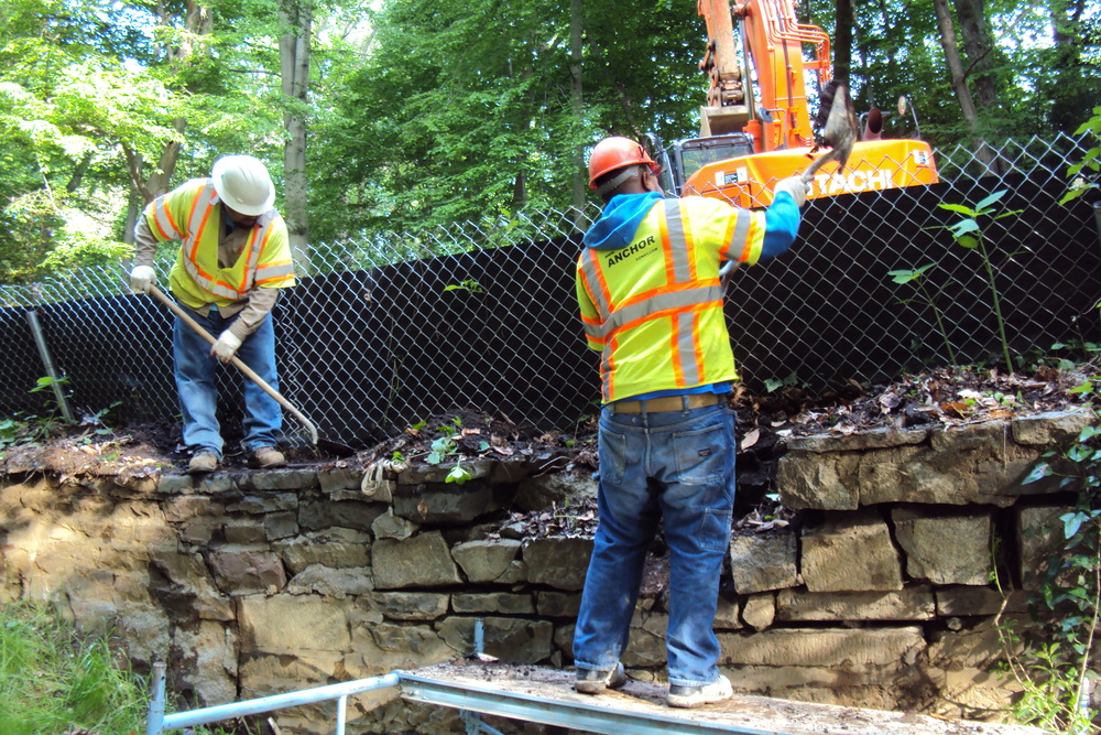 The crew resets the original stone headwall and applies fresh mortar at the joints