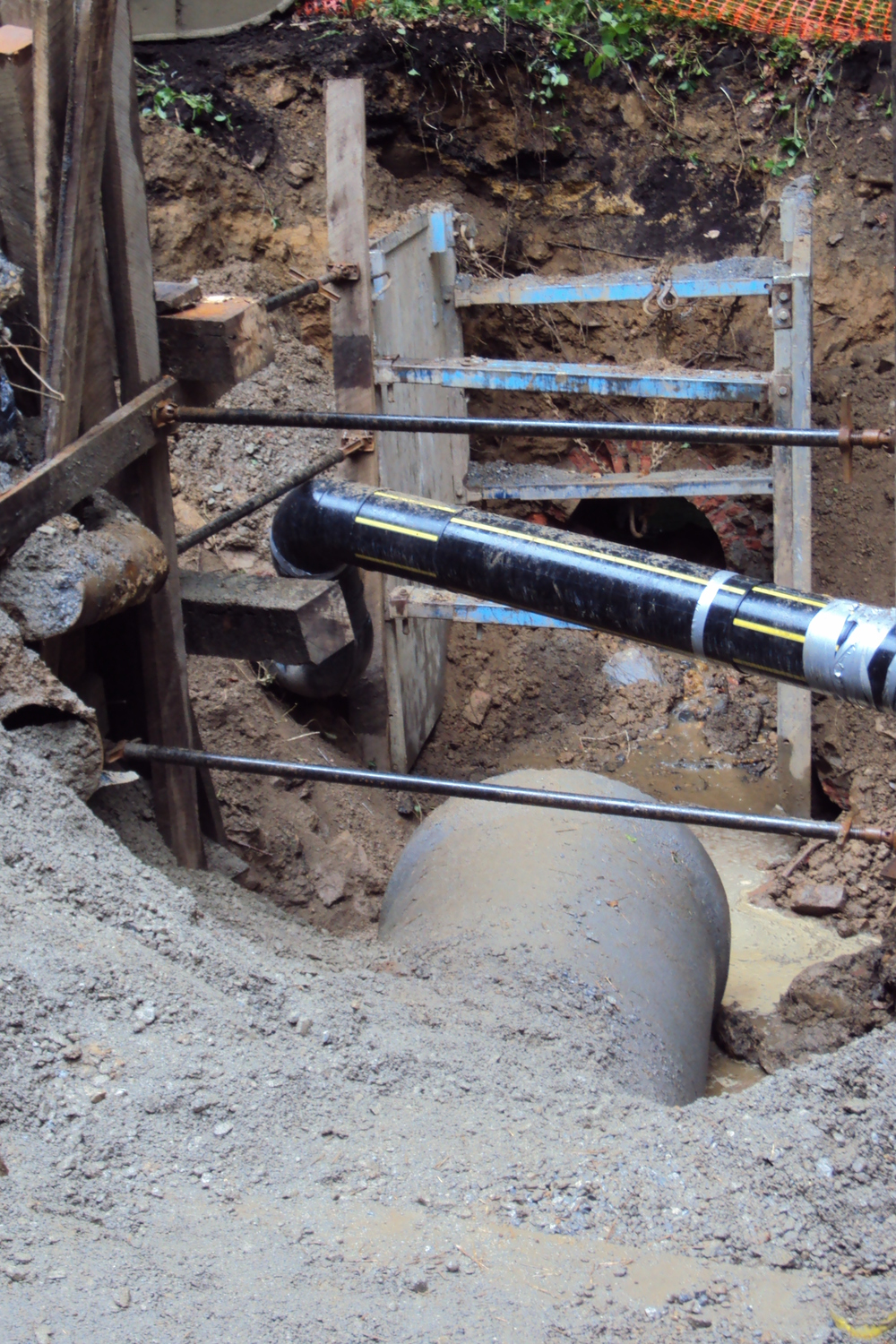 New concrete pipe is carefully installed under existing utility lines