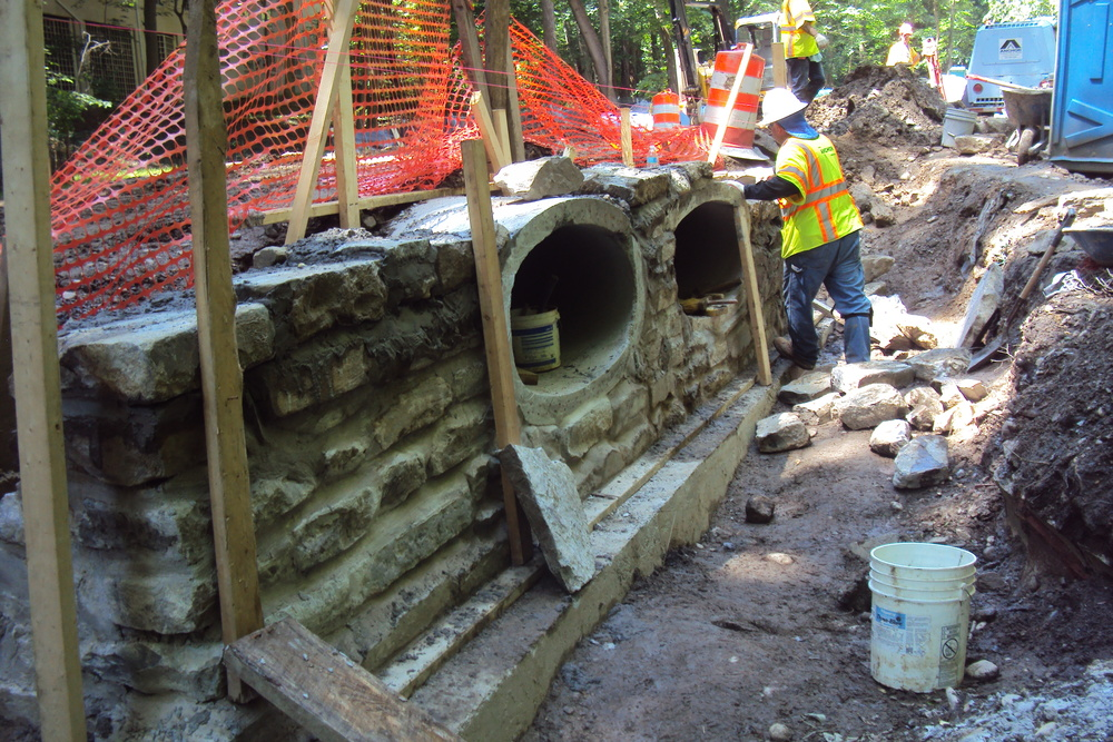 A stone mason aligns the next lift of salvaged stone to construct a stormwater headwall along the Klingle Valley Trail