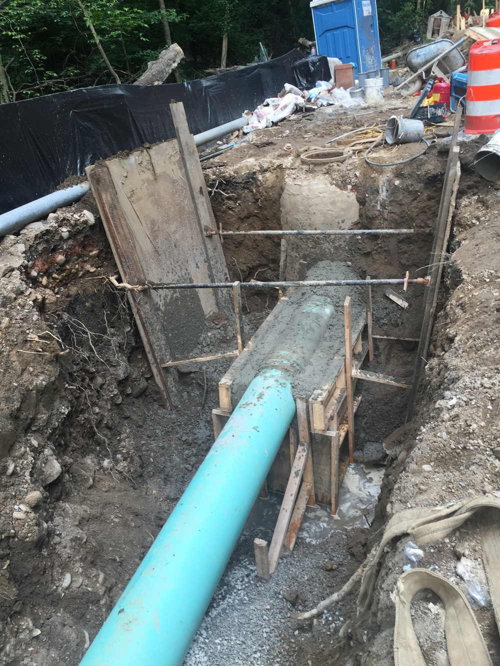The new drop connection to the manhole is encased with concrete