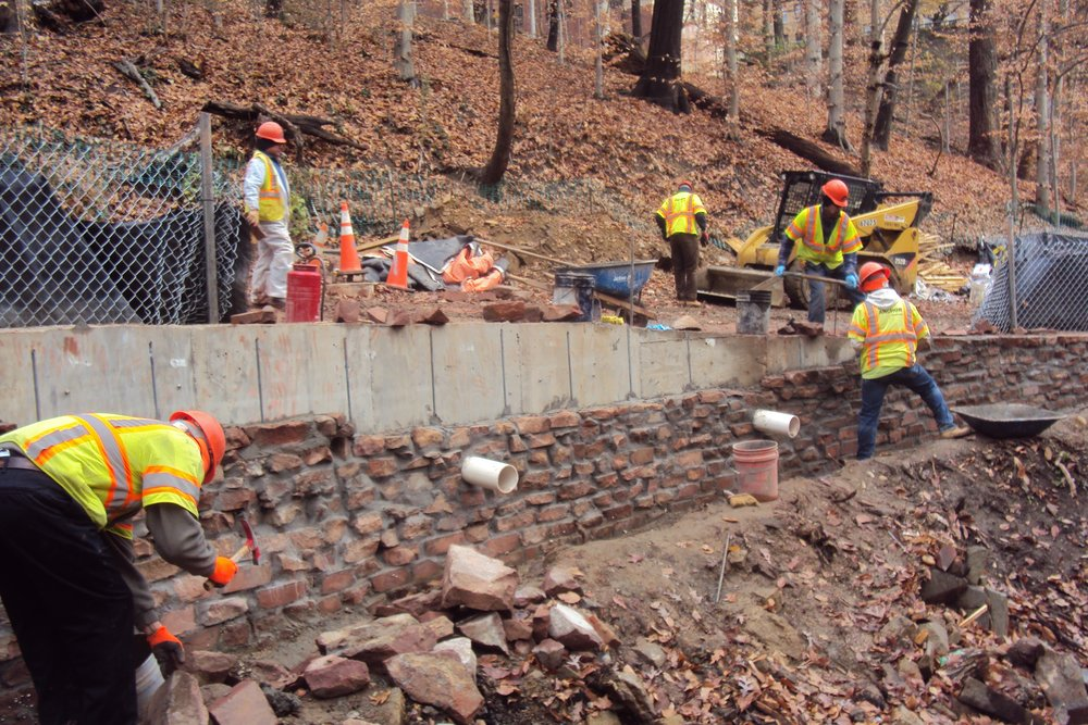 Construction crews utilize salvaged stone from within project limits to install a facade on the inside face of a newly placed concrete retaining wall adjacent to the stream.