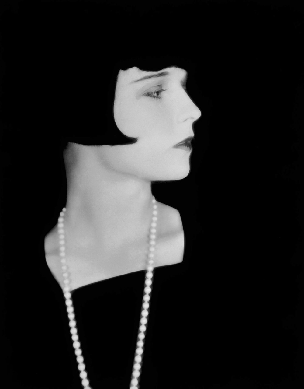 1929: American actress Louise Brooks (1906 - 1985) wearing a long necklace which stands out starkly against a black background. (Photo by Eugene Robert Richee)