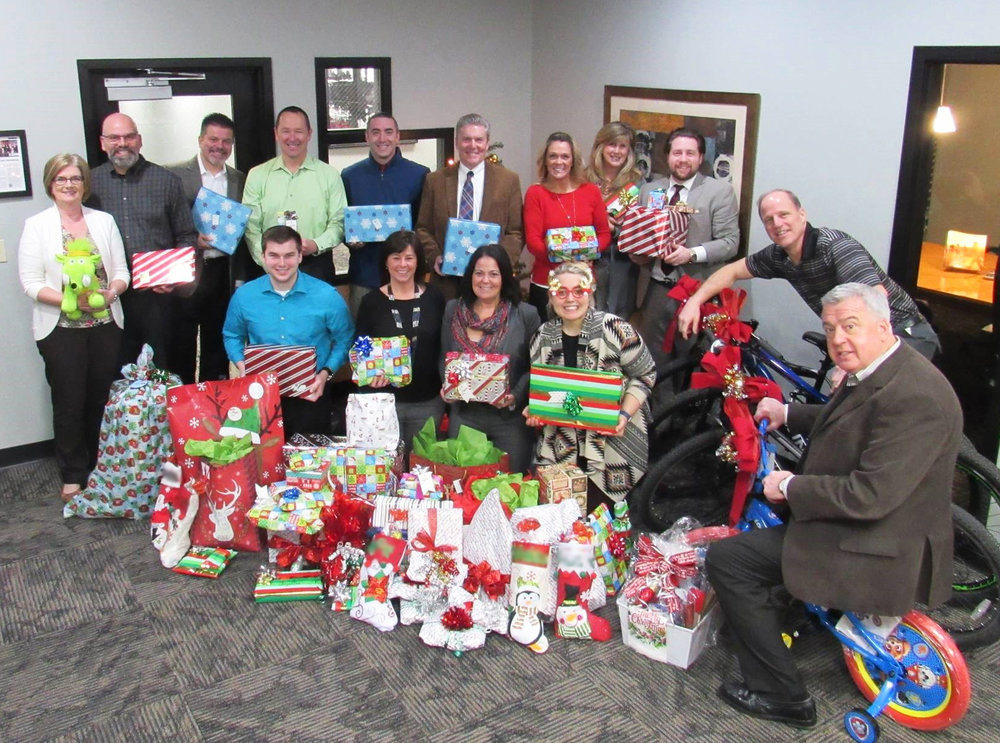 NAI Mid-Michigan/TMN Commercial professionals with holiday gifts for hosted family