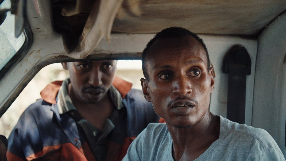 "Ivory dealer""X"" (outside car window) and poacher Lukas wait for the wildlife rangers to pass. From When Lambs Become Lions, directed by Jon Kasbe. Courtesy of Kasbe Films / The Documentary Group"