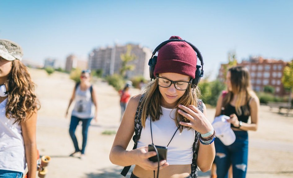 cff40928-368d-47ae-aec6-ebdecc459345-woman-headphones-looking-down-at-phone-walking-texting.jpg