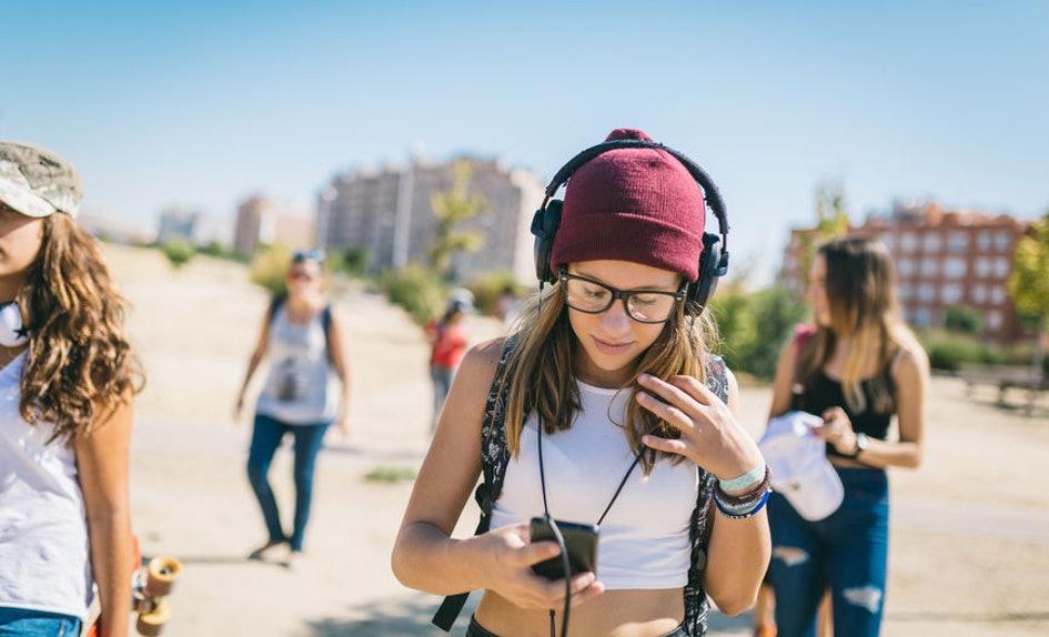 cff40928-368d-47ae-aec6-ebdecc459345-woman-headphones-looking-down-at-phone-walking-texting.jpg
