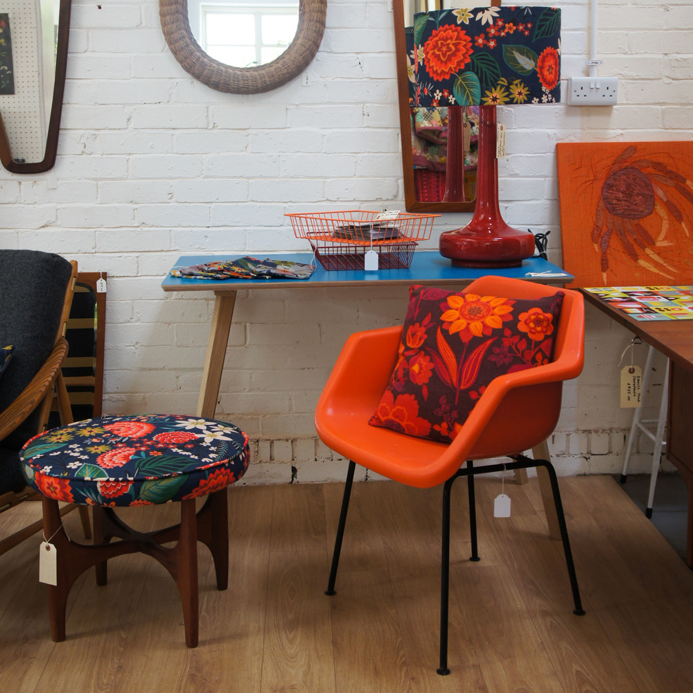 A bright orange chair by Robin Day for Hille and other pieces in our Carnation fabric by Brie Harrison.