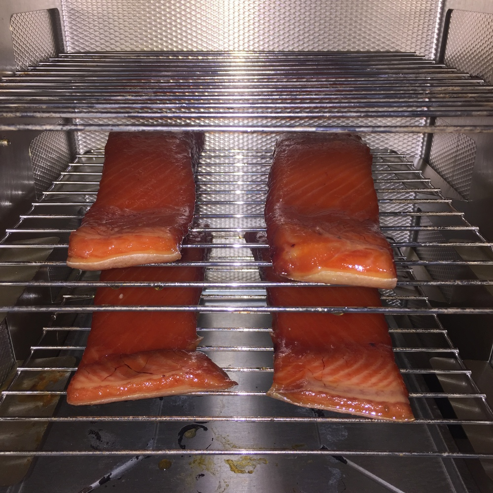 """Brined filets drying in the smoker with a fan to keep fresh air circulating. This drying process creates a film of brine on the outside of the fillets that allows the smoke to """"stick."""""""