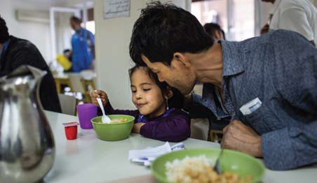 Rahmad and his daughter Rayhon eat lunch in the soup kitchen of Caritas Athens Refugee Centre, Greece.  Photo: Andrew McConnell/CRS