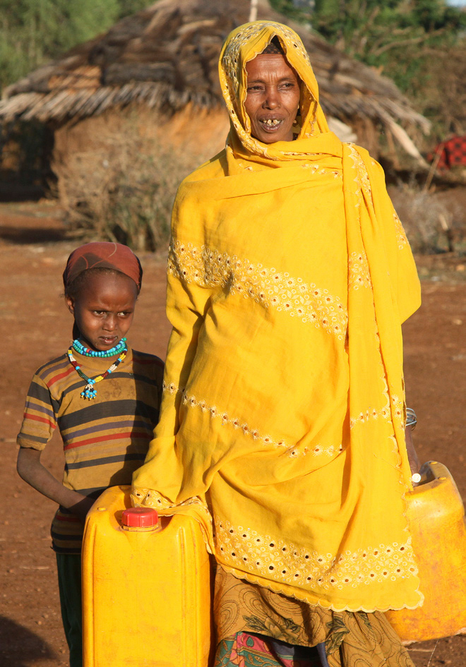A woman and her child carry water. Photo: Kim Pozniak/CRS