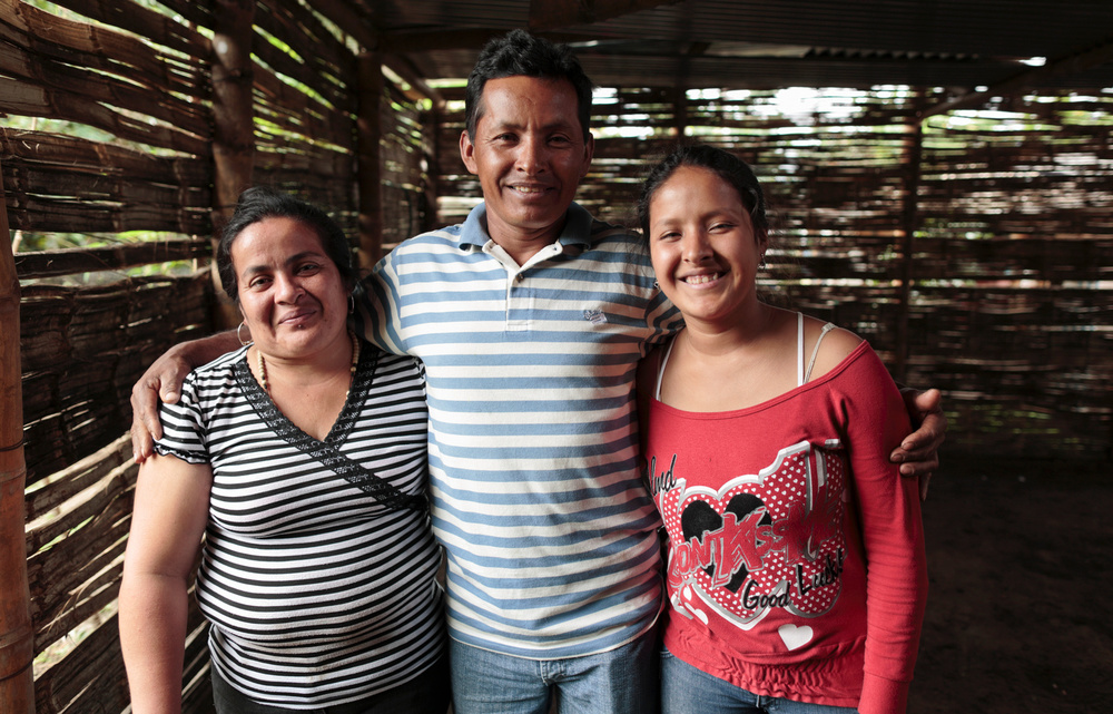 Maria poses with her parents in their new home in Colombia. Photo: CRS