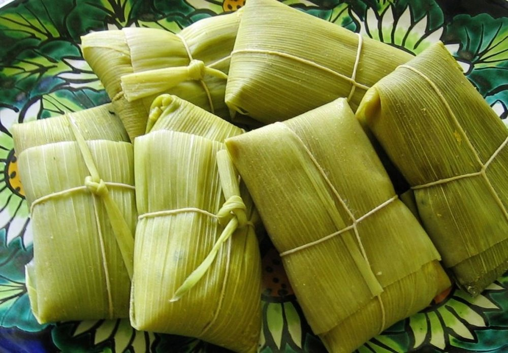 Humita  - Humitas are the Chilean version of tamales. Sweet or savory, Humitas are made with boiled flour and corn meal. Corn husks are stuffed with ground corn, basil, onion, and ground paprika. Humitas are usually cooked by steam or boiling water.