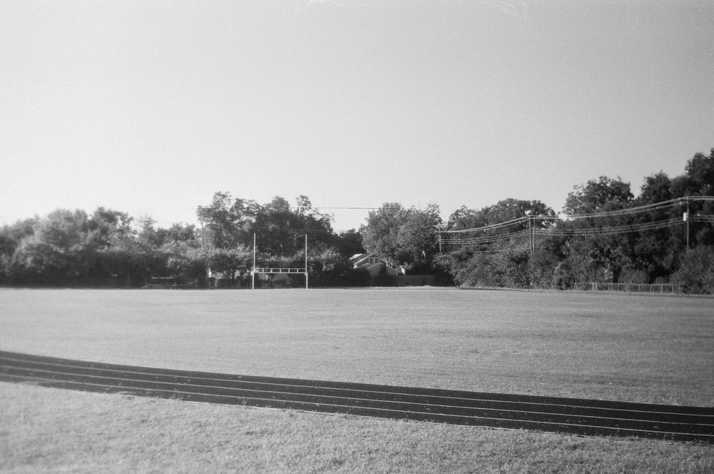 The football field. We played here as well before class stared. No pads or helmet were involved, you suffered with the injuries all day. Good times. 1980's Zorki 4 | Ilford HP5