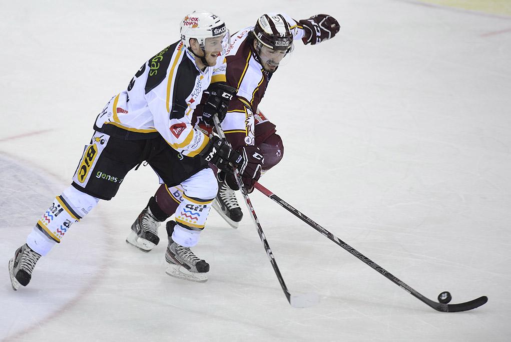 Le joueur luganais, Stefan Ulmer, gauche, a la lutte pour le puck avec le joueur genevois, Denis Hollenstein, droite, lors du 5eme match des quarts de finales de play-off du championnat suisse de hockey sur glace de National League LNA, entre le Geneve Servette HC et le HC Lugano, ce jeudi 20 mars 2014 a la patinoire des Vernets a Geneve. (KEYSTONE/Martial Trezzini)