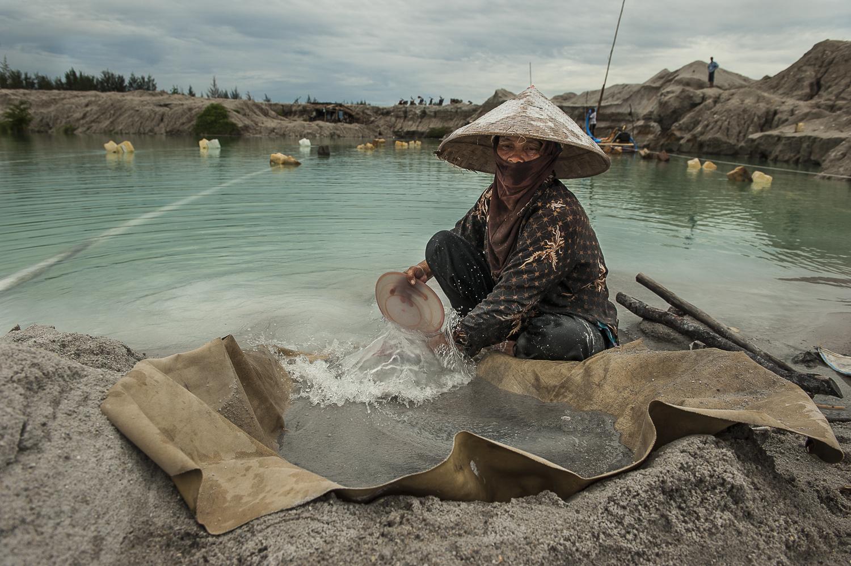 Ropiah, 45 ans, cherche de l'étain depuis huit ans dans une mine illégale sur la route de Pemali. Île de Bangka, Indonésie. Décembre 2012.