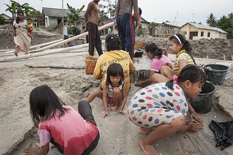 Le côté caché du succès es smartphones. des enfants de dix ans environ aident les mineurs à converser le minerai dans des seaux. Décembre 2012. Le côté caché du succès des smartphones. Mineurs-dont des enfants de 10 ans - tamisent du sable, le minerai d'étain trouvé est conservé dans des seaux. Les jeunes enfants jouent à côté des adultes qui travaillent, et apprennent ainsi des techniques minières. Tout le village de Batako travaille dans la mine illégale et dangereuse, à quelques mètres de leurs maisons. L'île de Bangka (Indonésie) est dévastée par des mines d'étain sauvages. La demande de l'étain a explosé à cause de son utilisation dans les smartphones et tablettes.