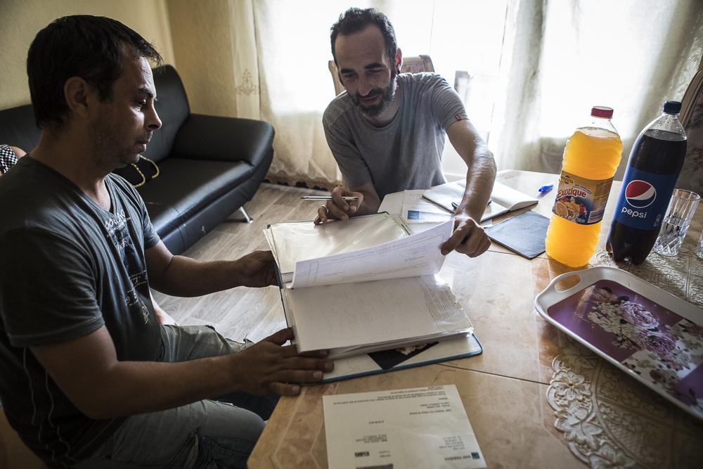 Jean-Marc (à droite), chargé d'accompagnement sur le projet Andatu, aide Marcel (à gauche) à décrypter sa facture d'électricité. Dardilly, France © Alberto Campi / Juillet 2015