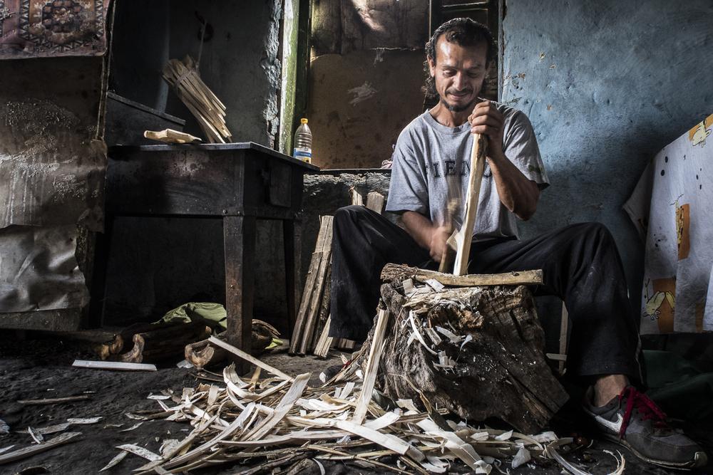 Calin Varga, dans sa petite maison en briques du bidonville de Tinca, fabrique des cuillères en bois, qu'il vend sur les marchés. Tinca, Roumanie. © Alberto Campi / Juillet 2015