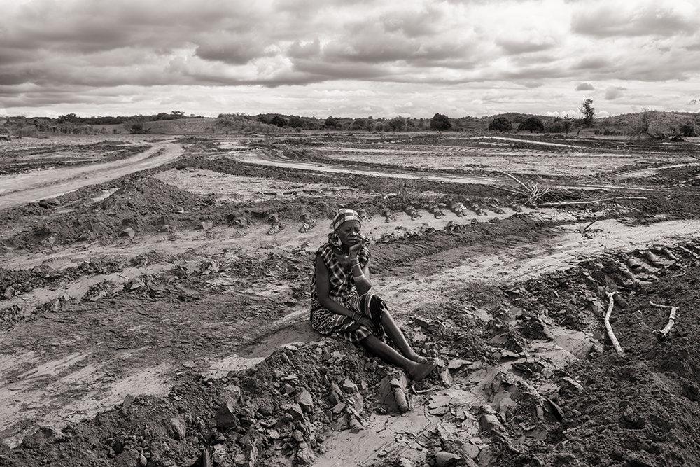 Falencia Ambulense, agricultrice, est assise dans son champ de mangues détruit par les bulldozers de Vale. Son village a été cédé par le gouvernement pour y établir une concession de charbon. © Benjamin Hoffmann / Inediz /Bagamoyo, 20 décembre 2013