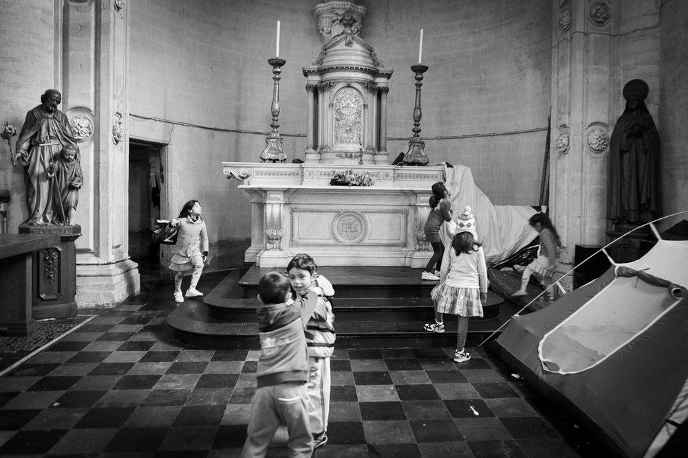 Des enfants jouent dans l'église bruxelloise du Béguinage occupée depuis quelques semaines par un collectif d'Afghans. © Alberto Campi / Bruxelles, 12 décembre 2013