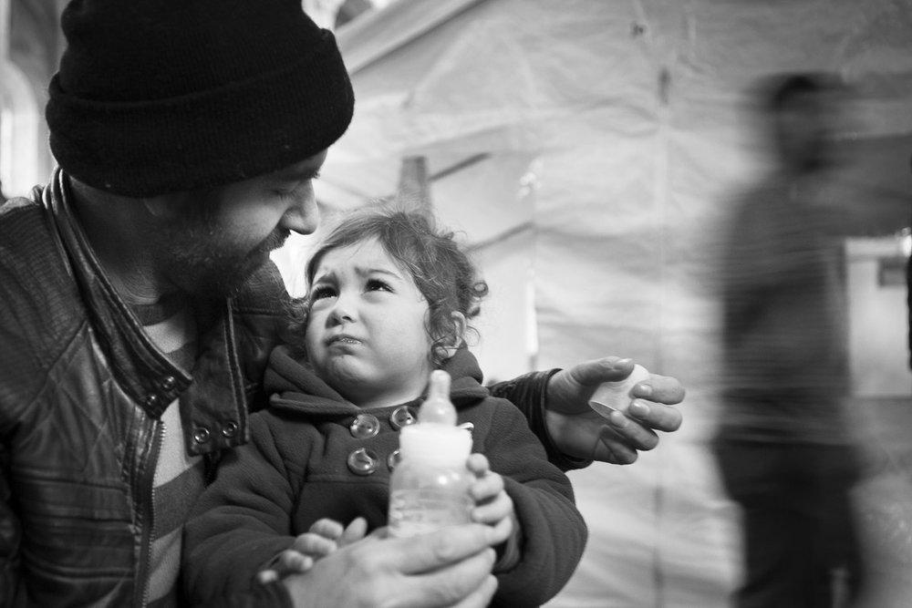 Aux premières heures d'une matinée très froide, un père nourrit sa fille. © Alberto Campi / Bruxelles, 12 décembre 2013