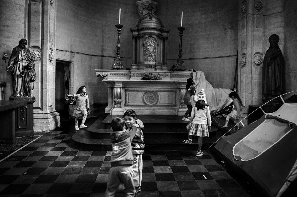 Des enfants jouent dans l'église bruxelloise du Béguinage occupée, fin 2013, par un collectif d'Afghans. © Alberto Campi / Bruxelles, 12 décembre 2013