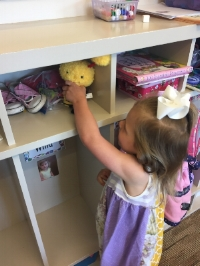 Willa putting Beena in the cubby