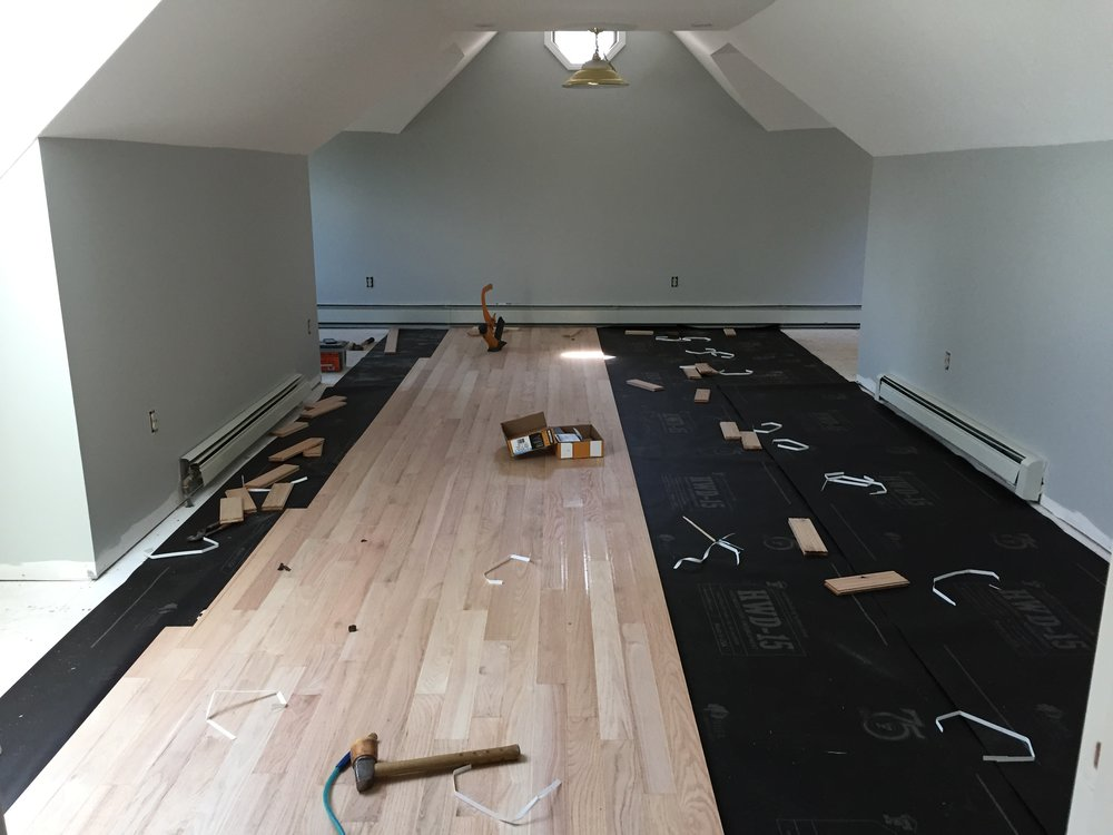 PROGRESS - TV room with new red oak flooring being installed (unstained)