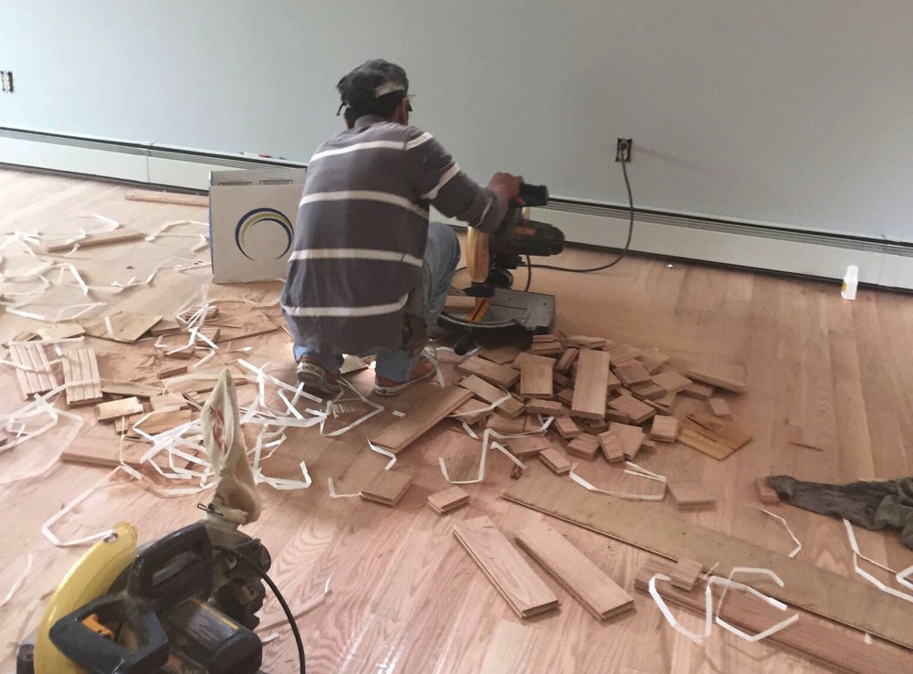 PROGRESS - TV room with new red oak flooring being cut down to fill in the gaps