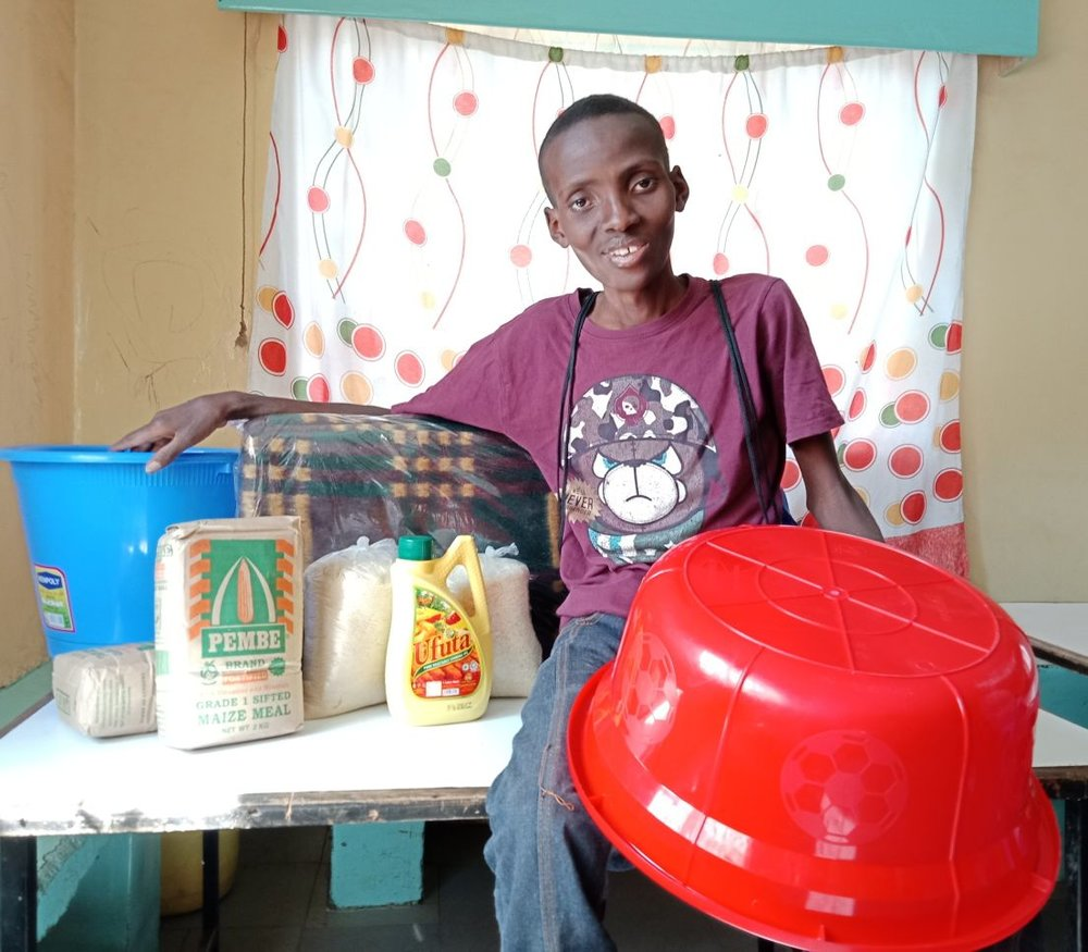 Isaac receiving supplies after the fire in January when he first joined the CARE for AIDS program