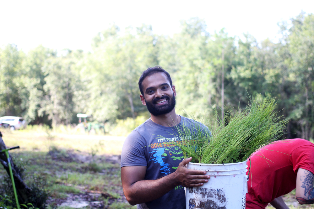 Abhi Lokesh, Founder of Fracture, holds a bucket of long leaf pine seedlings during a tree planting he and his team came out to support. They used the photos from this tree planting for a press release they announced to their network.