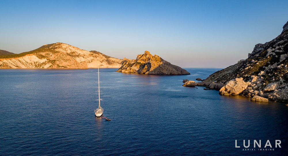 drone footage of yacht among islands