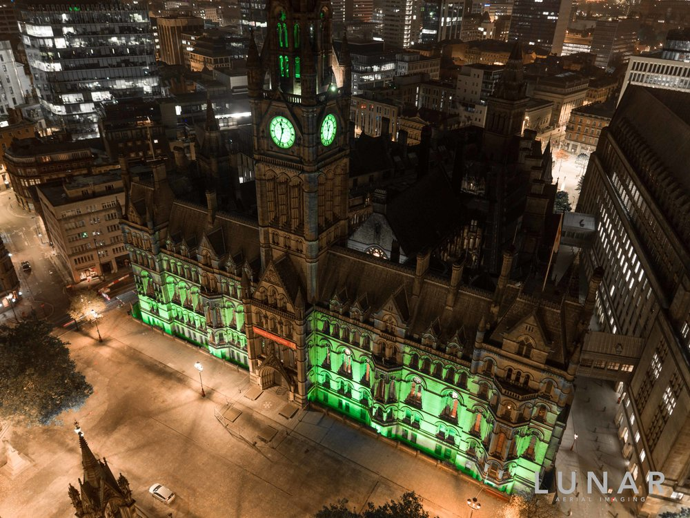 Aerial view of Manchester Town Hall lit up green for Halloween