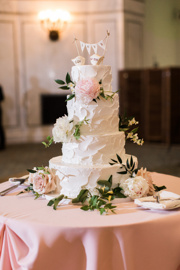 blush and white flowers on wedding cake