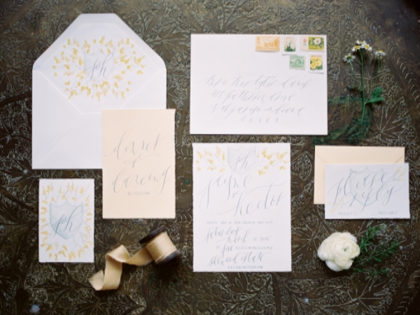 hand lettered wedding invitation with calligraphy in yellow and grey
