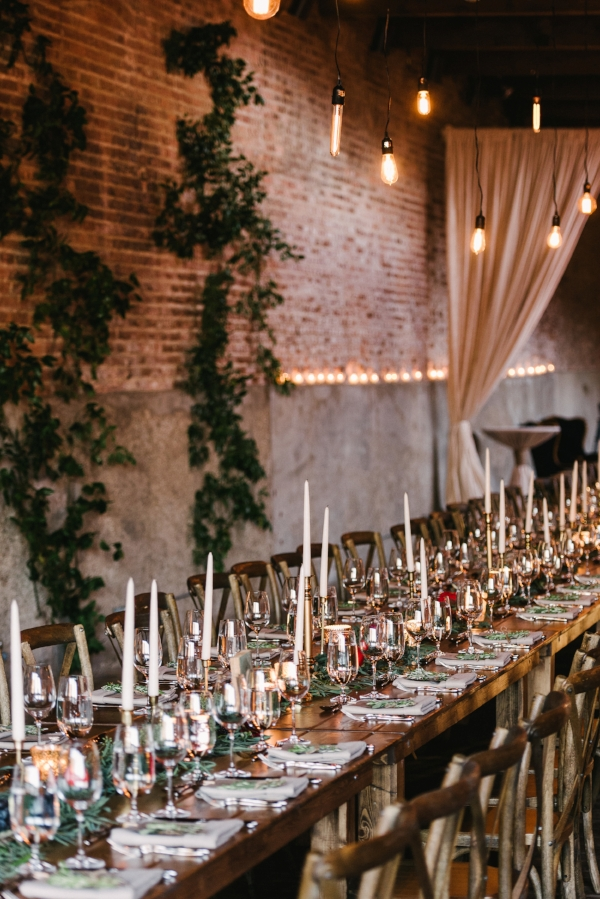 Indoor industrial wedding reception with farm tables, garland with fruits and flowers, greenery backdrop and industrial lighting by Foraged Floral