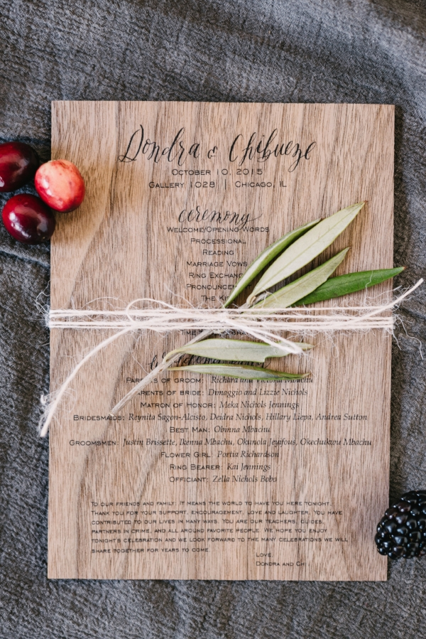 modern calligraphy wedding program on walnut stained wood with greenery and fruit accents