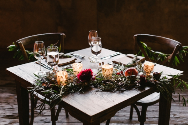 wedding sweetheart table decor with garland, burgundy peonies, candles and more on farm table by Foraged Floral